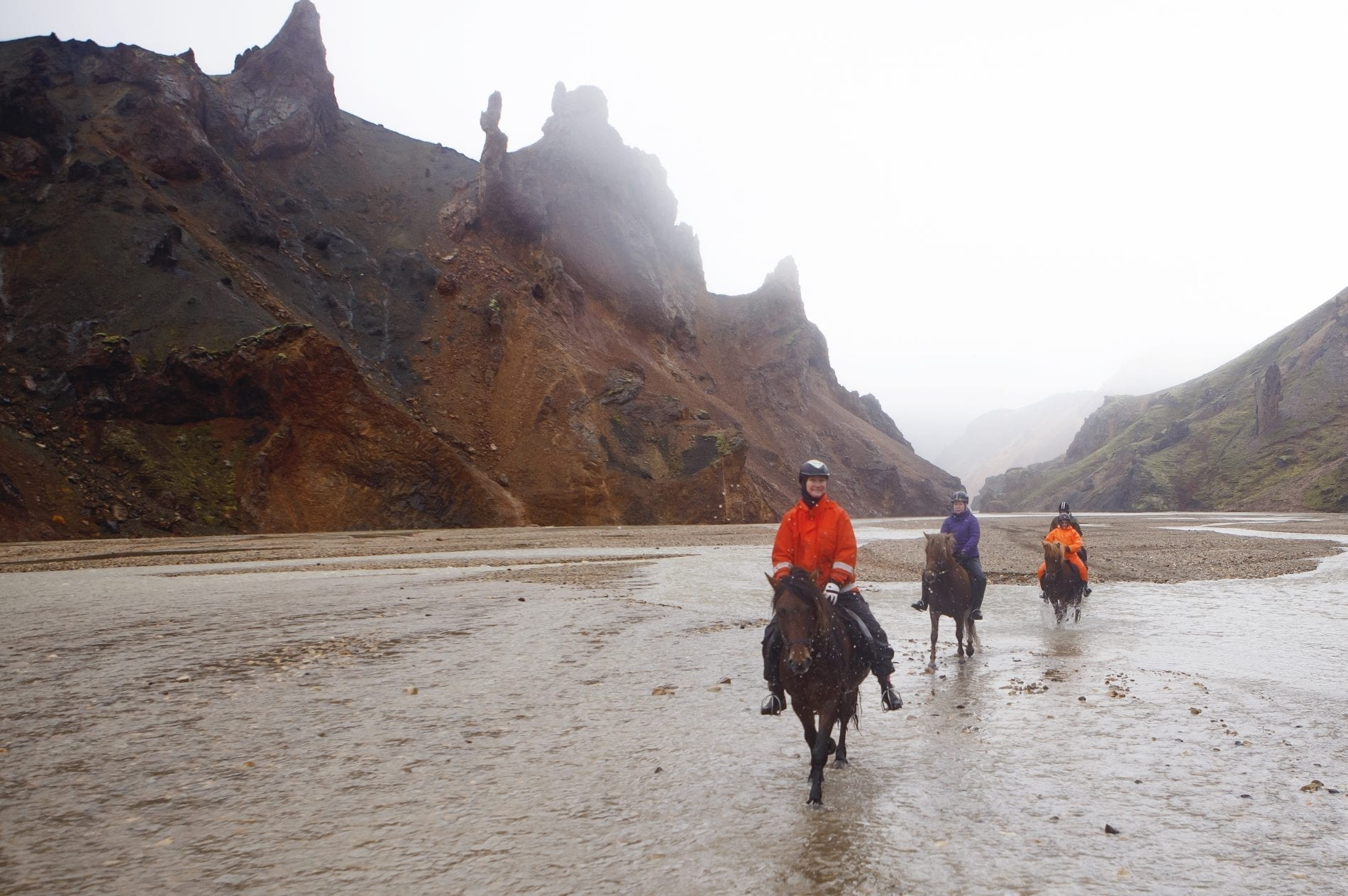 Three people horse riding for sheep round up in South Iceland