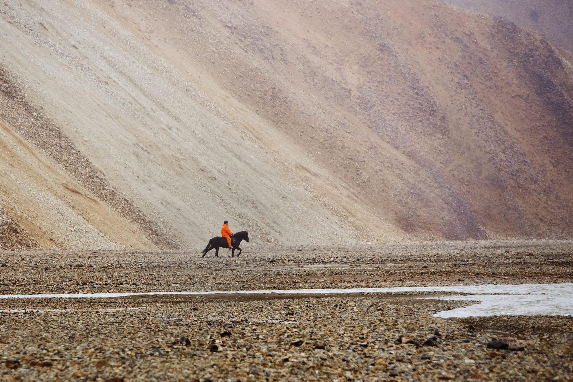 One man horseriding by the rhyolite monuntains of Landmannalaugar
