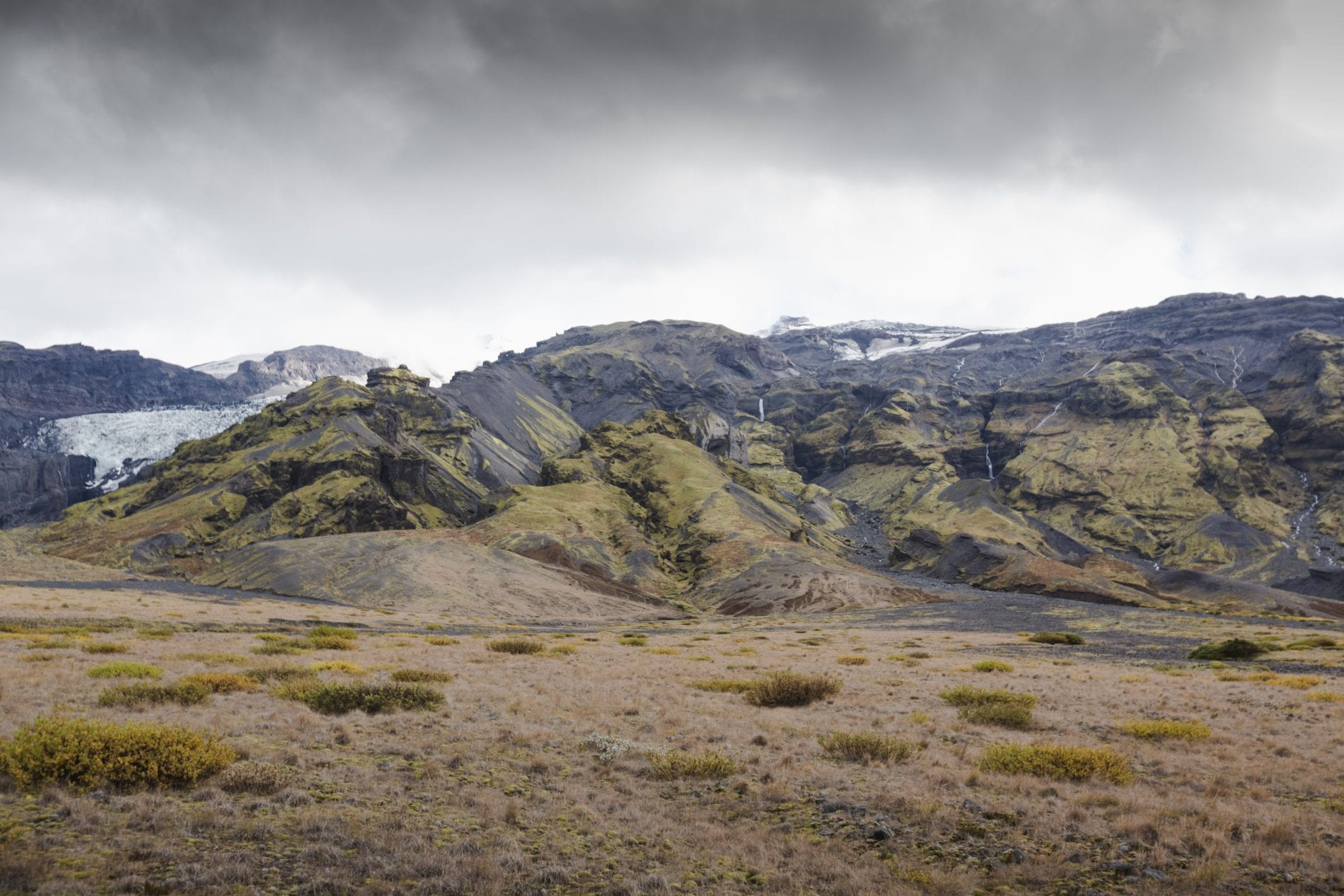 Snow, green shrubs and black rocks. The diverse landscape around Þórsmörk