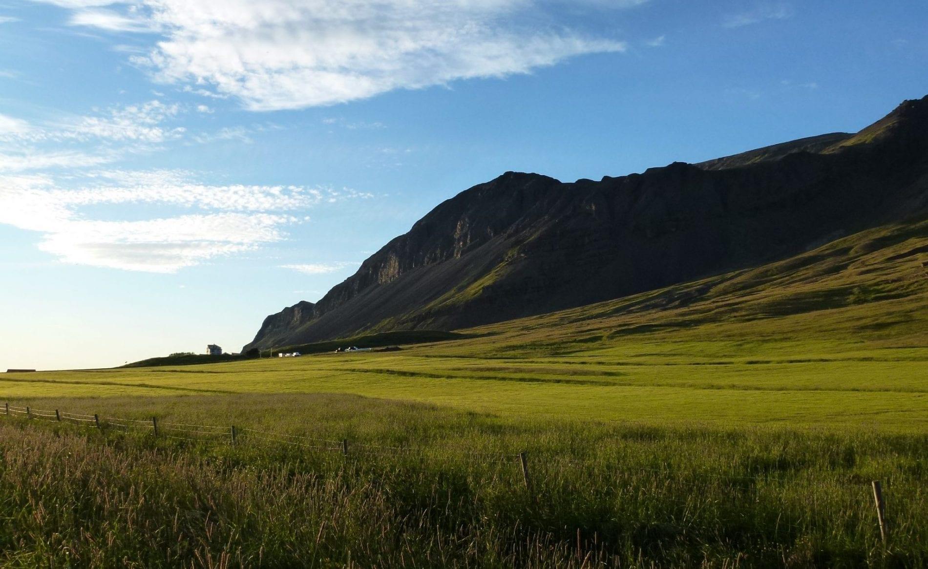Hvammur farm seen from a far. By its side a green fenced grass field reaching a mountain