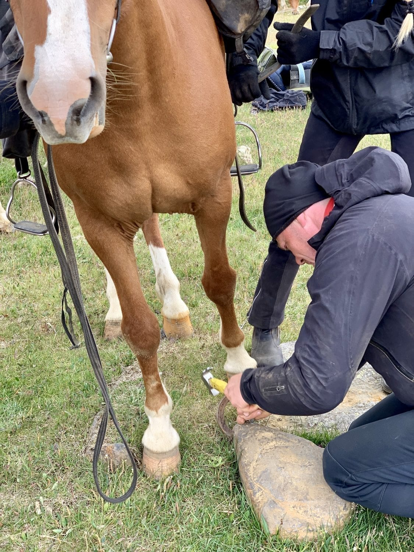 A man seen fixing a horse shoe
