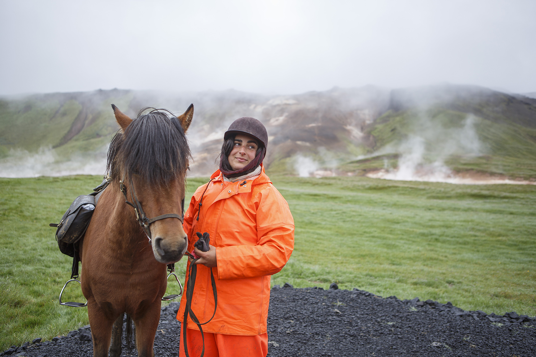 A woman with a riding helmet stands beside a horse with a bridle