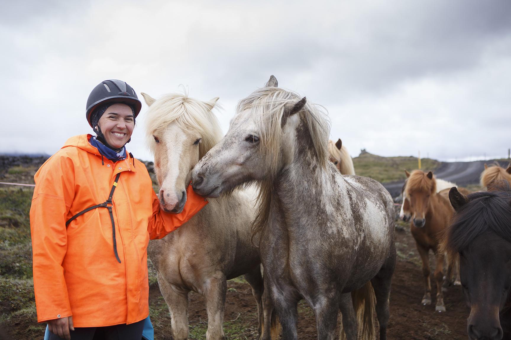 A smiling woman wearing an orange rain coat pets two horses