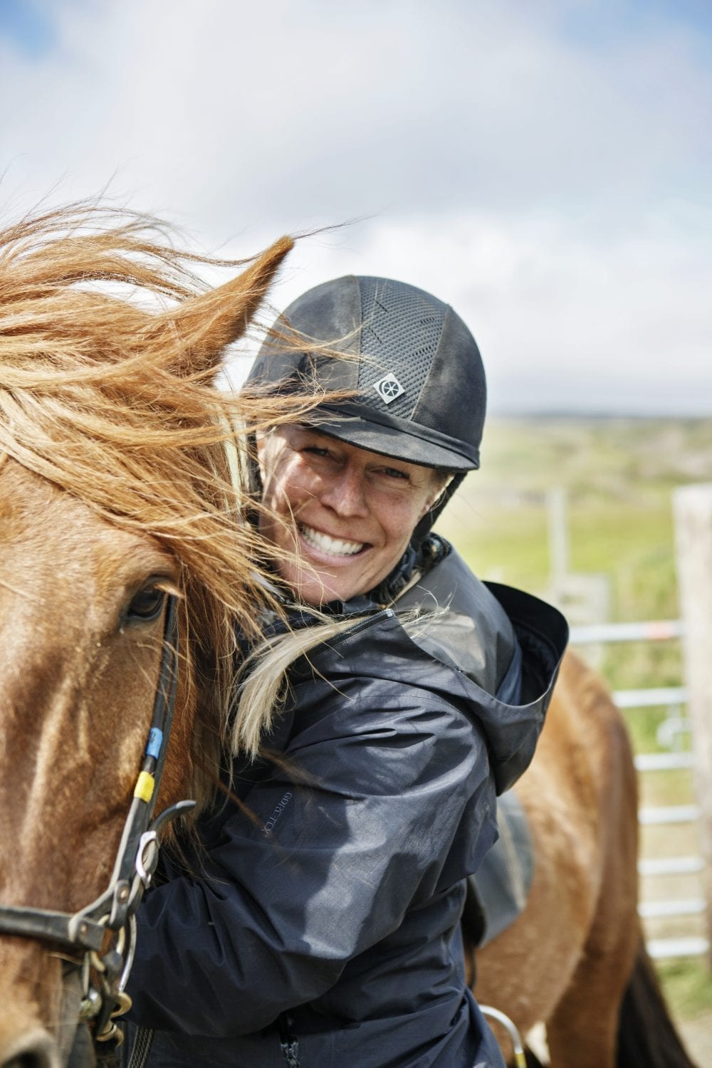 A smiling woman with a helmet embraces her horse