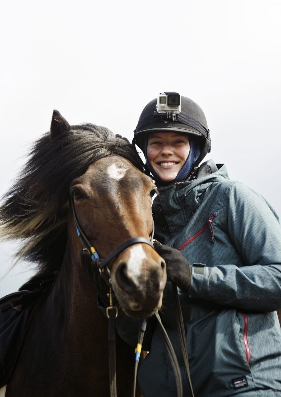 The radiant smile of a woman with her horse. Her camera is tied to the top of her helmet